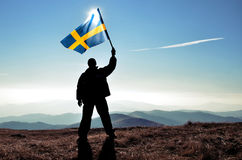 Successful silhouette man winner waving Sweden flag. On top of the mountain peak Royalty Free Stock Photography