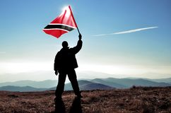 Successful silhouette man winner waving Trinidad and Tobago flag. On top of the mountain peak Royalty Free Stock Photos