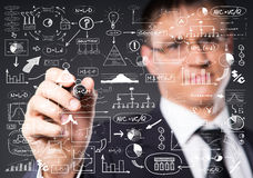 Successful and smart businessman writing imaginary text. Businessman working with a business plan. Financial, currency, technology and money concept Royalty Free Stock Images