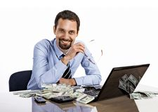 Successful smiling businessman with a lot of dollar stacks at the desk isolated on white background Stock Images