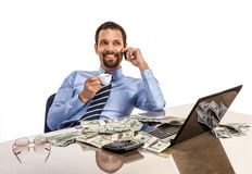 Successful smiling businessman relaxing and drinking coffee with a lot of dollar stacks at the desk isolated on white background Stock Image