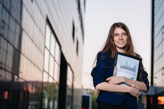 Successful smiling businessman, standing against the backdrop of buildings holding  folder with sales charts. City business woman Stock Photos