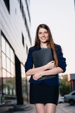 Successful smiling businessman, standing against the backdrop of buildings holding  folder with sales charts. City business woman Stock Photography