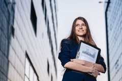 Successful smiling businessman, standing against the backdrop of buildings holding  folder with sales charts. City business woman Royalty Free Stock Photography