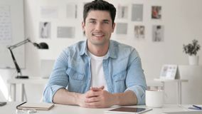 Successful Smiling Casual Young Man Sitting at Workplace