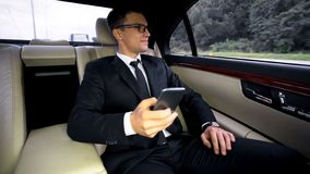 Successful smiling financial expert having ride to airport in luxury car, trip stock images