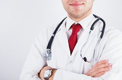 Successful smiling male doctor in medical coat with red tie and phonendoscope crossed his arms over chest. Concept of medical business stock photos
