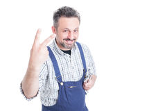 Successful smiling mechanic showing victory sign or number two. With advertising area isolated on white Royalty Free Stock Photos