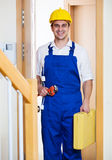 Successful specialist in helmet with tools at door Royalty Free Stock Image