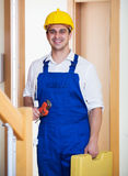 Successful specialist in helmet with tools at door Royalty Free Stock Photos