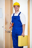 Successful specialist in helmet with tools at door. Happy handyman in uniform with tooling at house entrance Royalty Free Stock Photography