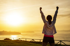 Successful sporty woman with arms up. Successful sporty woman raising arms towards golden beautiful sunset and sea. Female athlete celebrating sport success and stock photo