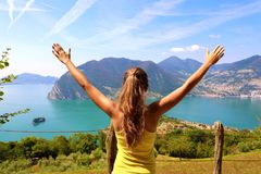 Successful sporty woman raising arms towards beautiful blue sky and lake. Female athlete celebrating sport success and goals. royalty free stock image