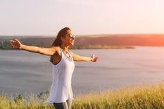 Successful sporty woman raising arms towards golden beautiful sunset Stock Images