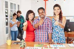 Successful startup team holding thumbs up. In international coworking office Stock Photo