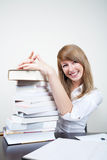 Successful student. Succesful smiling student sitting at table with stack of books Stock Images