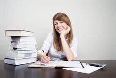 Successful student. Succesful student siiting at table smiling. With books on desk Stock Images