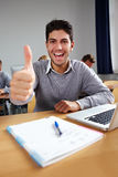 Successful student cheering. And holding his thumbs up Stock Photos