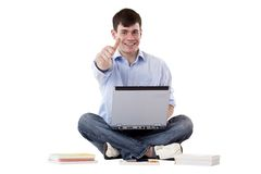 Successful student with computer shows thumb up Royalty Free Stock Photography