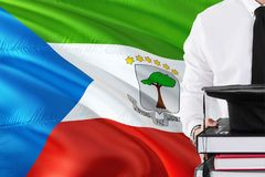 Successful student education concept. Holding books and graduation cap over Equatorial Guinea flag background.  stock images