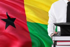 Successful student education concept. Holding books and graduation cap over Guinea Bissau flag background.  stock photo