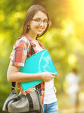Successful student girl with books in the Park on a Sunny day Stock Images