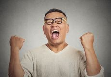 Successful student with glasses man winning, fists pumped. Closeup portrait successful student with glasses man winning, fists pumped celebrating success Stock Image