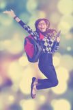 Successful student jumping with bokeh background. Cheerful female student celebrate her success and jumping over light glitter background Stock Photos