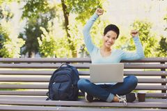 Attractive female student working on a laptop outside. Successful student outdoors. Winner woman with hands raised in the air sitting with crossed legs on the Stock Photography