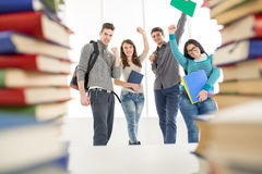 Successful Students. Group of cheerful students standing among the books with arms raised in a fist in school hall and looking at camera Stock Images
