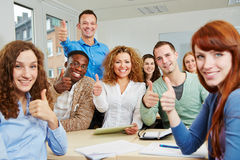 Successful students holding thumbs Stock Photography