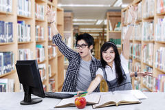 Successful students raise hands in library Royalty Free Stock Images