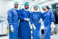 Successful surgeon team standing in operating room. Portrait of successful surgeon team standing in operating room. happy medical workers in surgical uniforms in Stock Photo