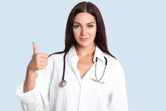 Successful talented female therapist raises thumb and shows ok sign, dressed in white robe, looks seriously at camera, stands agai stock image