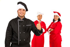 Successful  team of chefs. Successful team of three chefs with teacher chef in front of image giving thumbs Royalty Free Stock Photography