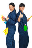 Successful team of cleaning women. Successful team of cleaning workers women standing back to back holding products and giving thumbs up isolated on white royalty free stock photo