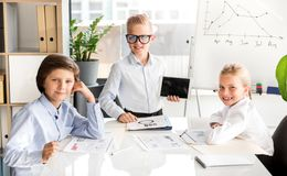 Optimistic kids are expressing gladness. Successful team collaboration concept. Portrait of cute children are looking at camera with joy while working in office royalty free stock image
