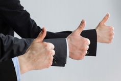 Successful team in dark suits showing thumbs up Royalty Free Stock Photo