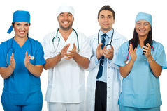 Successful team of doctors clapping together. Successful team of four different doctors applauding together isolated on white background,check also royalty free stock photo