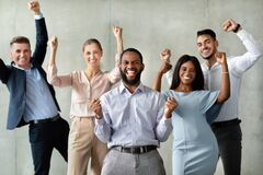 Successful Team. Group Of Multiracial Colleagues Celebrating Business Achievement With Raised Fists. Successful Team Concept. Group Of Multiracial Colleagues