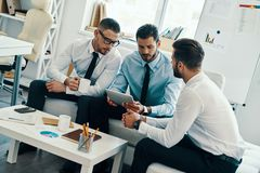 Successful team. Group of young modern men in formalwear working using digital tablet while sitting in the office royalty free stock photos