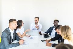 Successful team leader and business owner leading informal in-house business meeting. Businessman working on laptop in foreground stock photography