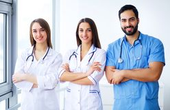 Successful team of medical doctors are looking at camera and smiling while standing in hospital stock image