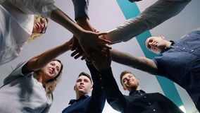 Successful team in office: many hands holding together standing in circle. Team building concept.