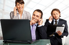 Successful team phones and laptop. Business team of three on their phones with a laptop Royalty Free Stock Photography