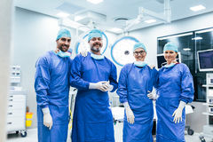 Successful team of surgeon standing in operating room. Portrait of successful team of surgeon standing in operating room, ready to work on a patient. Medical Royalty Free Stock Photography