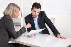Successful teamwork: businessman and woman sitting at desk talki. Business men and businesswoman sitting at desk talking about reports and finance Stock Images