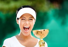 Successful tennis player won the match. Tennis player won the cup at the sport tournament. Award Royalty Free Stock Photos