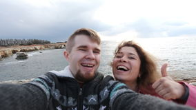 Successful traveling couple in love taking a selfie on the beach stock video