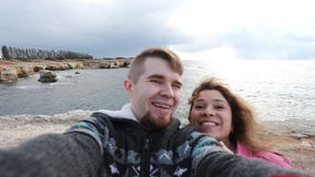 Successful traveling couple in love taking a selfie on the beach stock footage